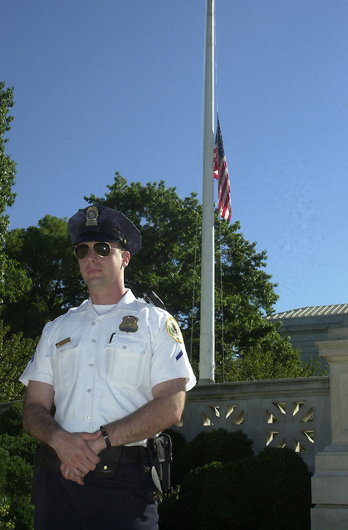 4dayafter091201 -- Policeman Mackie stands guard at the U.S. Supreme Court in front of a flag at half-mast..Mackie said he heard the Pentagon attack as it happened yesterday.