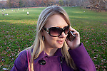 Young Woman walking and talking on her cell phone in Central Park NYC