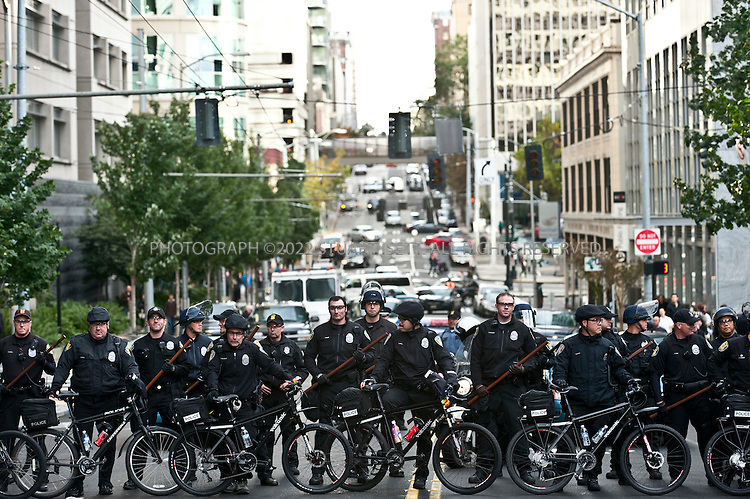 10/22/2011--Seattle, WA, USA..Police for a  barrier outside a police station during a protest march in downtown Seattle. Occupy Seattle, a spin off of the Occupy Wall Street protests in New York City, joined an anti-police brutality march in downtown Seattle with over 500 protesters, including a few black masked anarchists and other radicals. ..The Occupy Seattle protest has attempted to set up a base in Seattle's Westlake Park in the heart of the city but the Seattle Police Department has arrested anyone attempting to set up tents...©2011 Stuart Isett. All rights reserved.