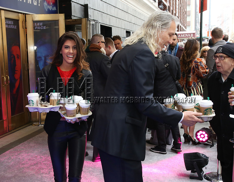 """Corey Brunish and Jessica Rose Brunish bring coffee to the press photographers at the Broadway Opening Night Arrivals for """"Angels In America"""" - Part One and Part Two at the Neil Simon Theatre on March 25, 2018 in New York City."""