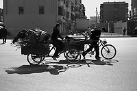 Daytime landscape view of a man and a woman driving tricycles in the street in Dàtóng Shì Chéng Qū in Shānxī Province, China  © LAN