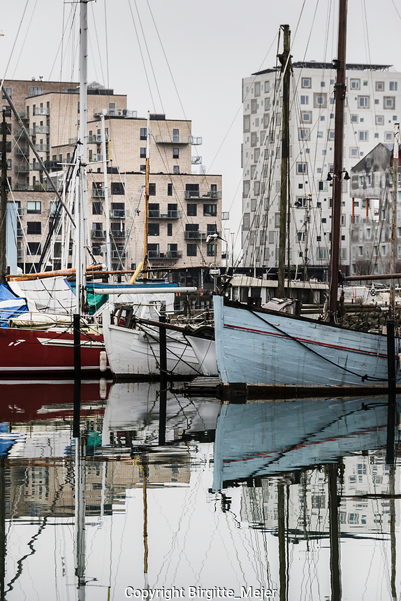 Colorfull wooden Sailboats in the grey winter in Scandinavia, with modern Architecture rising in the background, and the boats and their masts mirroring in the water.