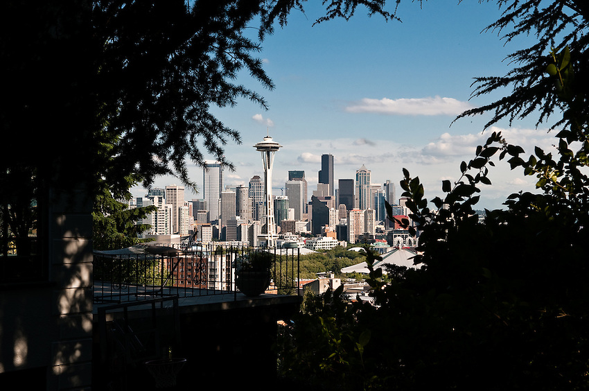 Seattle skyline photo framed by trees and include the Space Needle. Photograph by Robert Wade.