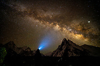 The star filled night sky above giant mountains of the Karakoram, Pakistan.