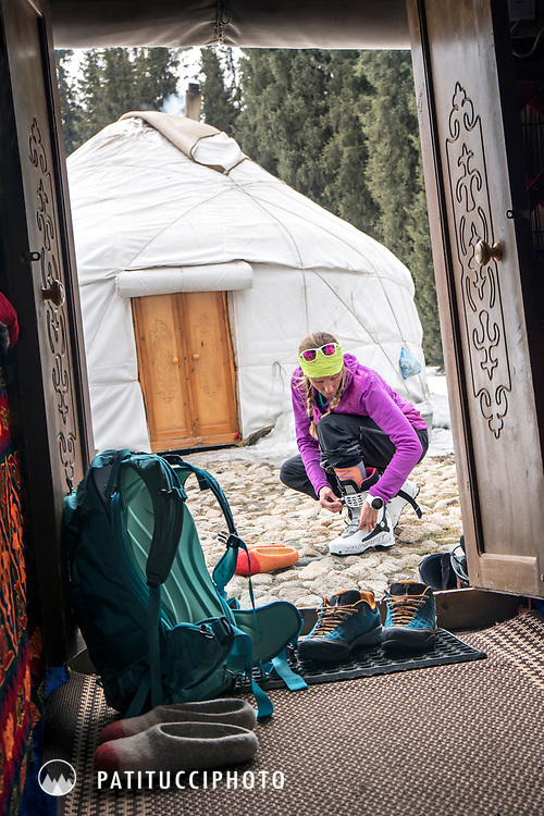 A woman is framed in the door of a yurt putting her ski boots on while on a ski trip in Kyrgyzstan