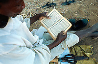 Sudan. West Darfur. Kerenek. An old man, dressed with white clothes, sits on the ground and reads the holy book, the Koran, during the day at ramadan period. © 2004 Didier Ruef