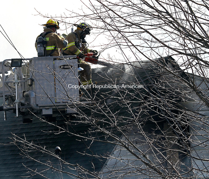 Thomaston, CT-26 March 2012-032612CM02-  Firefighters cut a hole on on the roof at the residence on the corner of High Street Ext and Mason Hill where a fire broke out Monday afternoon in Thomaston.   Christopher Massa Republican-American