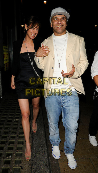 MIKA (Goldie's Girlfriend) & GOLDIE (Clifford Joseph Price).At Jason Statham's party, Planet Hollywood, London, England, UK, August 15th 2009..full length black dress couple holding hands cream beige blazer suit jacket jeans cap hat white trainers gold rings .CAP/CAN.©Can Nguyen/Capital Pictures