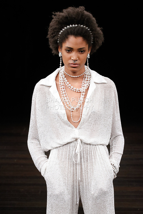 """Model walks runway in a """"Nevad"""" bridal jumpsuit from the Naeem Khan Bridal Spring 2018 collection, on April 21, 2017; during New York Bridal Fashion Week."""