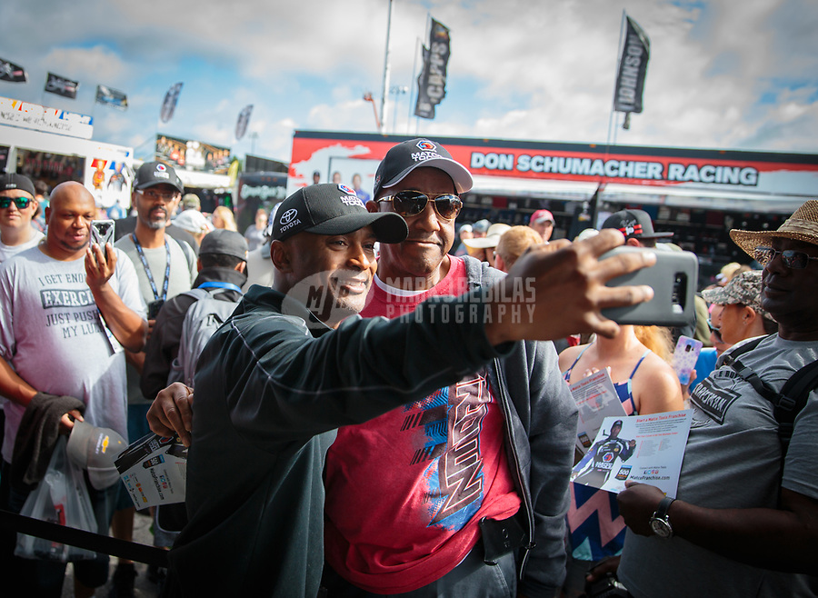 May 5, 2019; Commerce, GA, USA; NHRA top fuel driver Antron Brown (left) takes a selfie photo with a fan in the pits during the Southern Nationals at Atlanta Dragway. Mandatory Credit: Mark J. Rebilas-USA TODAY Sports