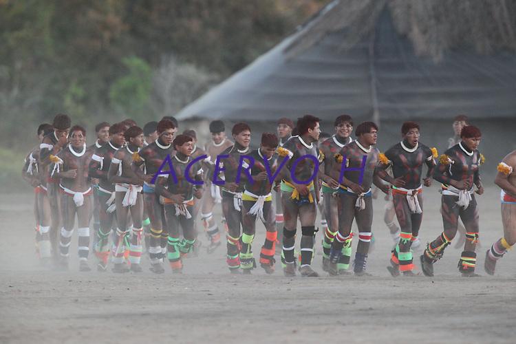 """Cerimônia do Kwarup na aldeia Kamaiurá, no Parque indígena Xingu.<br /> <br /> O Kwarup (nome do ritual na língua kamaiurá) é considerado o grande emblema do Alto Xingu e trata-se de uma cerimônia funerária, que envolve mitos de criação da humanidade, a classificação hierárquica nos grupos, a iniciação das jovens e as relações entre as aldeias. Ao longo dos meses que se seguem até o encerramento ocorrem, não necessariamente todos os dias, dois tipos de danças e o toque de longas flautas (uruá, na língua dos Kamaiurá), sempre retribuídos com oferecimento de alimentos pelos """"donos"""" do Kwarup. O foco de orientação dessas atividades rituais é sempre a cerca sobre a sepultura. No pátio da aldeia promotora do rito, cada falecido homenageado é representado por uma seção de tronco de cerca de dois metros. São de uma espécie vegetal que tem distintas denominações conforme as diferentes línguas xinguanas. Os Kamaiurá a chamam de Kwarup, a mesma madeira com que o herói mítico fez as mulheres que enviou para se casarem com o jaguar. Os troncos são colocados um ao lado do outro, de pé, embutidos em buracos de 50 cm de fundo. São pintados e ornamentados com adornos plumários e cintos masculinos. A única distinção entre os troncos que representam homens e os que representam mulheres é que os primeiros são guarnecidos com mechas de algodão não fiado. Também os homens comuns falecidos têm direito a ser representados por troncos, porém menos grossos e com ornamentação mais simples. Os espíritos dos mortos homenageados ficam junto aos troncos na última noite do rito e a isto se reduz a sua participação. Ao anoitecer, acendem-se fogueiras diante de cada tronco do Kwarup. Enquanto os moradores da aldeia anfitriã se revezam, velando os troncos e chorando os falecidos homenageados, os visitantes, cada acampamento por sua vez, entram na aldeia trazendo achas de pindaíba para remanejar as fogueiras, numa cena movimentada e tensa.<br /> <br /> Fonte:"""
