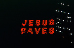 """Jesus Saves"" neon sign in lit up at night in urban setting"