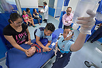 Nurse Jazmine Gino-Gino (right) checks the flow on an IV she just inserted in the hand of ten-month old Johan in the emergency room of the Mary Johnston Hospital in Manila, Philippines. Holding the boy down is Nurse Brian Grape Maningding. Johan's mother, Mirakel Guarin, comforts the boy.<br /> <br /> The hospital is supported by United Methodist Women.