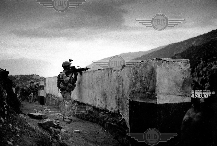 American troops in the Korengal Valley duck behind a school wall during an attack/ambush. This is one of the most remote and hostile places in Afghanistan, and where there is fierce Taliban resistance.