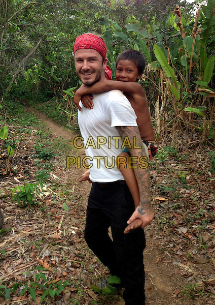 David Beckham in the Amazon Rainforest with child from local tribe<br /> in David Beckham Into the Unknown (2014)<br /> *Filmstill - Editorial Use Only*<br /> CAP/FB<br /> Image supplied by Capital Pictures