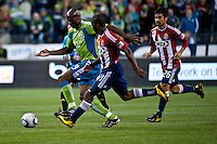 Blaise Nkufo (L) of the Seattle Sounders works the ball against Chivas USA defenders Michael Lahoud (C) and Paulo Nagamura (R) at the XBox 360 Pitch at Quest Field in Seattle, WA on October 15, 2010. The Sounders defeated Chivas USA 2-1.