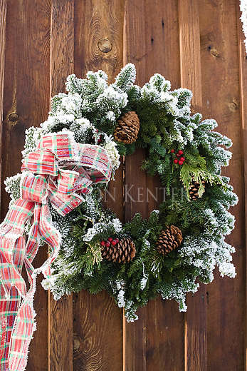 A frost coated Christmas wreath on the side of a barn in Missoula Montana