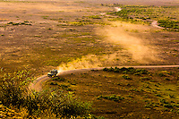 A safari vehicle trailed by dust, Amboseli National Park, Kenya