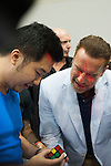 US actor and former California governor, Arnold Schwarzenegger gestures as he observes a youth solve a Rubik's Cube puzzle during the officiation of the Arnold Classic Asia Multi-Sport Festival in Hong Kong. Photo by Marcio Machado / Power Sport Images