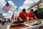 Belleville Fire Department firefighter Ryan Mahoney (left) and pipeman Ray Winchester prepare slabs of ribs at the first Belleville Brew & Que in downtown Belleville.  This first-ever event featured a Barbecue Challenge and craft beer tasting at 20 downtown businesses. Three bands played during the event, which ran from 11 a.m. to 9 p.m.  The Craft Beer Walk ran from noon to 4 p.m. at select downtown Belleville merchants.  For a $15 ticket, you could have 16 tastings of a wide variety of craft beers.  The Barbecue Challenge ran all day, with vendors selling samples of two meats for $1, or a meaty rib bone for $2.