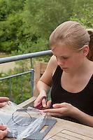 Mädchen, Kind bastelt eine Becherlupe, Beobachtungsgefäß aus 2 durchsichtigen Plastikbecher, einem Stück Styropor und Frischhaltefolie. 6. Schritt: Bechergroßer Kreis wird aus Frischhaltefolie ausgeschnitten