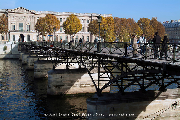 People crossing the Pont des Arts over the Seine, Paris, France.