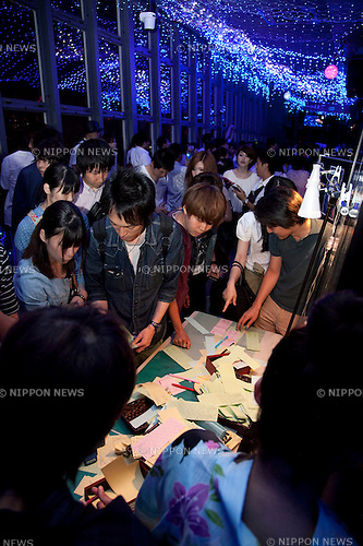 July 7, 2012, Tokyo, Japan - Tokyo Tower visitors write their wishes on colorful papers (Tanzaku) and then hang them on bamboo stalks at Tanabata festival on July 7th at the main observatory. The annual celebration of Tanabata in Japan and has been held since the Edo era. It celebrates the meeting of two lovers Orihime and Hikoboshi, according to legend the Milky Way separates these lovers, and may only meet once a year on the seventh day of the seventh month of calendar. (Photo by Rodrigo Reyes Marin/AFLO)...
