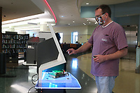 Kevin La Born uses a self check out kiosk Monday, May 18, 2020, at the Fayetteville Public Library.  The library opened with limited hours and social distancing restrictions for the first time since mid-March because of the covid-19 pandemic. Twenty two patrons visited the library within the first 10 minutes of opening. The library will continue to offer online catalog items for curbside pick-up. Library materials can now be returned in drive-by drop boxes. Check out nwaonline.com/200519Daily/ and nwadg.com/photos for a photo gallery.<br /> (NWA Democrat-Gazette/David Gottschalk)