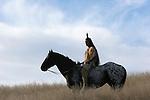 A young Native American Indain horseback riding a horse bareback