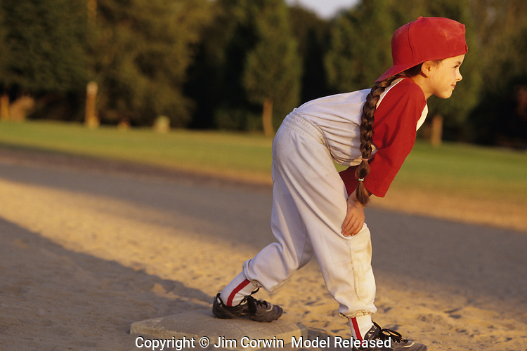 Young girl (7 years old) little league baseball player running bases toward second base with smile on her face, sunset light, Woodinville, Washington State USA  MR