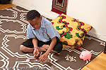 8 year old boy counting sorting coins with piggy bank on floor nearby horizontal