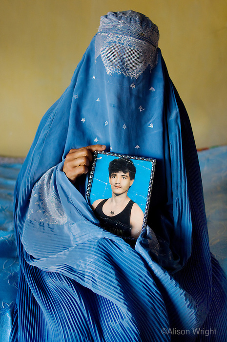 Afghanistan, Kabul. Shakiva, women in burka in her bedroom, holding photo of slain husband.  <br /> Bamiyan, Afghanistan 2007 (R)<br /> Women who had once been doctors, lawyers and professionals in this country are now beaten by their husbands for a violation as menial as showing an inch of skin on their wrists. I was impressed with the resiliency of Afghan women who were so determined to take reclaim their lives. Many secretly meet in backroom classes learning to read so they know if they&rsquo;re buying a box of milk or cement from the local store, or how to handle money so they can count change from a taxi ride. Rarely will you ever see a woman driving a car. Others learn vocational skills such as weaving, sewing and computer work. In Kabul, I attended a judo class for young girls. In Bamiyan, where there is even a female governor, I met a small contingency of women police officers, as they practiced shooting their AK-47s and hand guns at the rifle range. Education, women have come to realize, is a major step of empowerment that no one can take away from them.