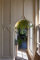 A gothic doorway in the panelled wall of the drawing room leads into the conservatory