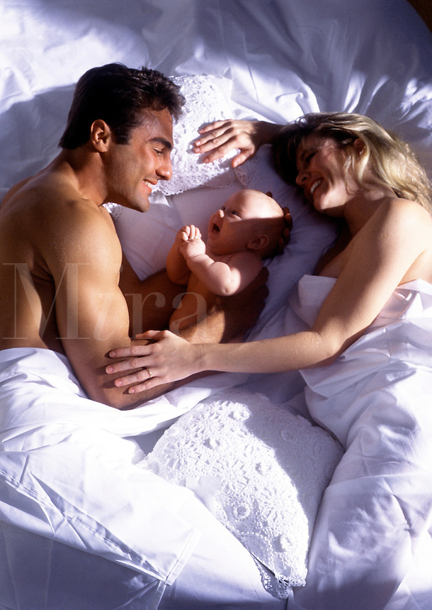 A young family shares an intimate moment in bed together.