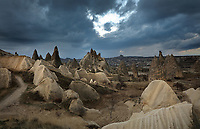 Fairy chimneys and cave dwellings in the Goreme Valley, in Goreme National Park, between Goreme and Uchisar, in Nevsehir province, Cappadocia, Central Anatolia, Turkey. The rock formations here were made by erosion of the soft volcanic tuff created by ash from volcanic eruptions millions of years ago. The Goreme Valley also contains cave dwellings, underground towns and churches, carved out of the rock in the Byzantine period. This area forms part of the Goreme National Park and the Rock Sites of Cappadocia UNESCO World Heritage Site. Picture by Manuel Cohen