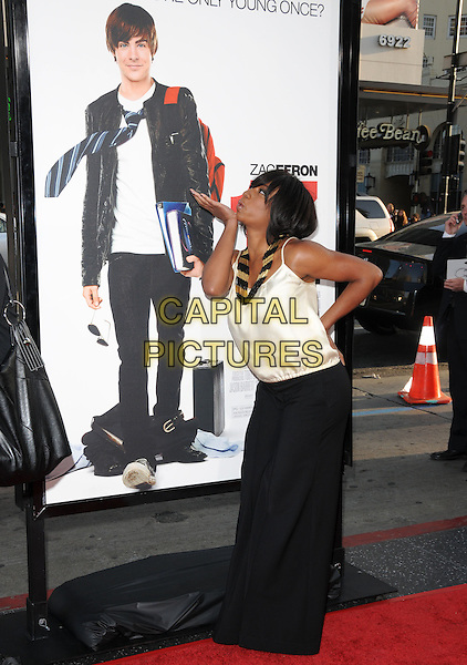 "MONIQUE COLEMAN.The L.A. premiere of ""17 Again"" held at The Grauman's Chinese Theatre in Hollywood, California, USA. .April 14th, 2009.full length white top black trousers wide leg flared hand on hip profile poster blowing kiss .CAP/DVS.©Debbie VanStory/Capital Pictures."