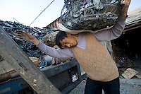 Wu Yuenxi, a migrant worker from Sichuan province carries a load of tin extracted from electronic trash in the town in nanyang, China.