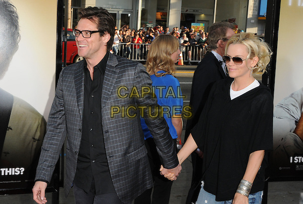 "JIM CARREY & JENNY McCARTHY.The Warner Brother Pictures' L.A. Premiere of ""The Hangover"" held at The Grauman's Chinese Theatre in Hollywood, California, USA. .June 2nd, 2009.half length couple holding hands black grey gray top jacket sunglasses shades glasses bracelet cuff .CAP/DVS.©Debbie VanStory/Capital Pictures."