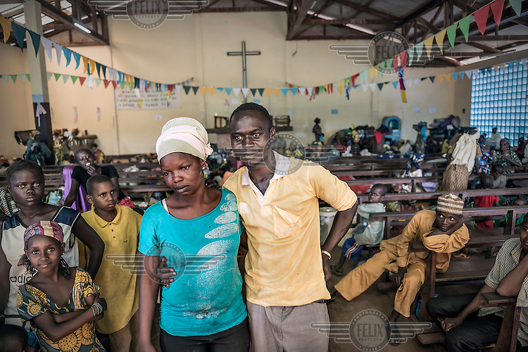 Ousmane Hamidou and Pulchrie Kossy standing among the Muslim women and children who crowd the floor of a Catholic Church in Boali. The priest gave them sanctuary from Christian vigillante groups seeking to attack and kill Muslims in response to the 2013 Seleka rebellion. Pulchrie is a Christian and being married to a Muslim man has joined them as she would also be a target of the CHristian vigillantes. Seleka, a predominantly Muslim rebel group led by Michel Djotodia, toppled the government of President Francios Bozize. Djotodia declared that Seleka would be disbanded but as law and order collapsed the ex-Seleka fighters roamed the country committing atrocities against the civilian population. In response a vigillante group, calling themselves Anti-Balaka (Anti-Machete), sought to defend their lives and property but they then began to take reprisals against the Muslim population and the conflict became increasingly sectarian. French and Chadian peacekeeping forces have struggled to contain the situation and the smaller Muslim population began to flee the country.