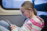 USA, New York State, New York City, Girl (10-11) sitting in train with earphones and listening music