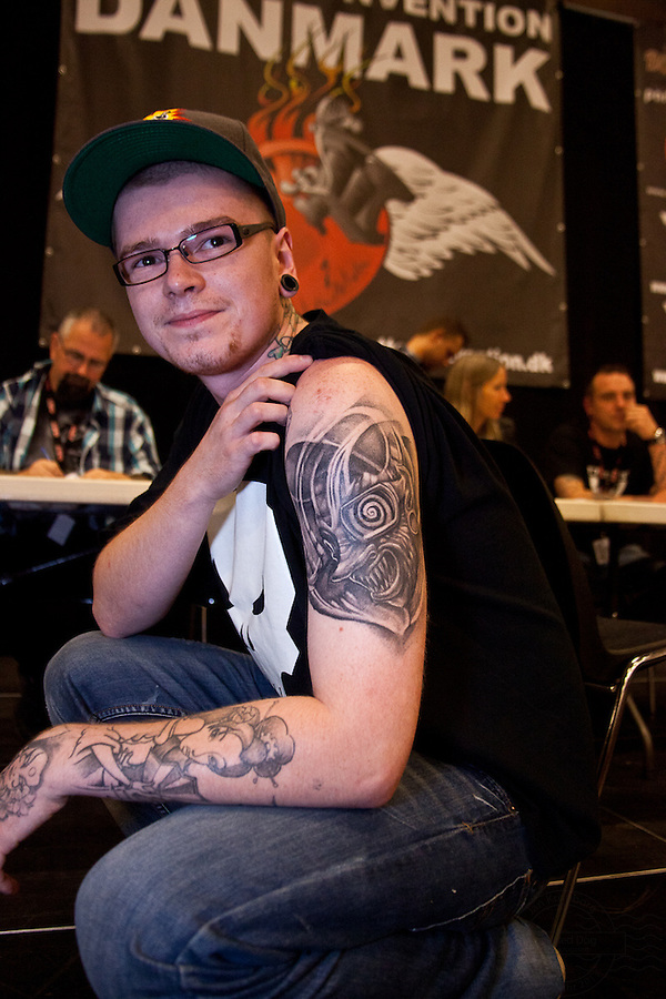 Tattoo Convention in Kolding 2011. Arranged by BodyMod.dk<br /> Young man showing cartoon face in black and grey tattooed on shoulder.