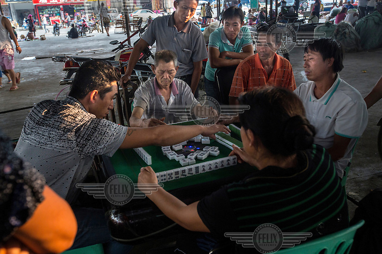 Men play Chinese Mahjong in the market in Mong La. <br /> The town of Mong La on the Burma - China border in western Burma (Myanmar) is technically in Burma but relies on most infrastructure - electricity, telecommunications - on neighbouring China. The main currency used here is the Chinese yuan. The town is in the middle of the so-called &quot;Golden Triangle&quot; and specialises in gambling and the sale of poached and endangered species. Tiger skins, rhino horns, pangolins and other creatures are freely traded here and many are available to eat. Prostitution is rife and just outside the town a bear farm keeps between 500 and 600 bears which are kept in captivity for their bile which is harvested for medicinal use.