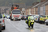 Pictured: The Banksy is transported with police escort through Dyffryn Road on a flat bed lorry. Wednesday 29 May 2019<br /> Re: Contractors are working to move Banksy's Season Greeting, now owned by John Brandler, which appeared on a garage wall in Port Talbot, to a new location in the same town in south Wales, UK.