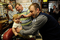 STAFF PHOTO FLIP PUTTHOFF <br /> FIRST HAIRCUT<br /> Gary Townzen, left, watches fellow barber Vic Bradford give Will Fox, age 8 months, his first haircut while Will's dad, Spencer Fox, right assists on Saturday Dec. 20 2014 during the annual free haircut day at Townzen Barbershop in downtown Rogers. Donations were accepted to benefit Samaritan Community Center.