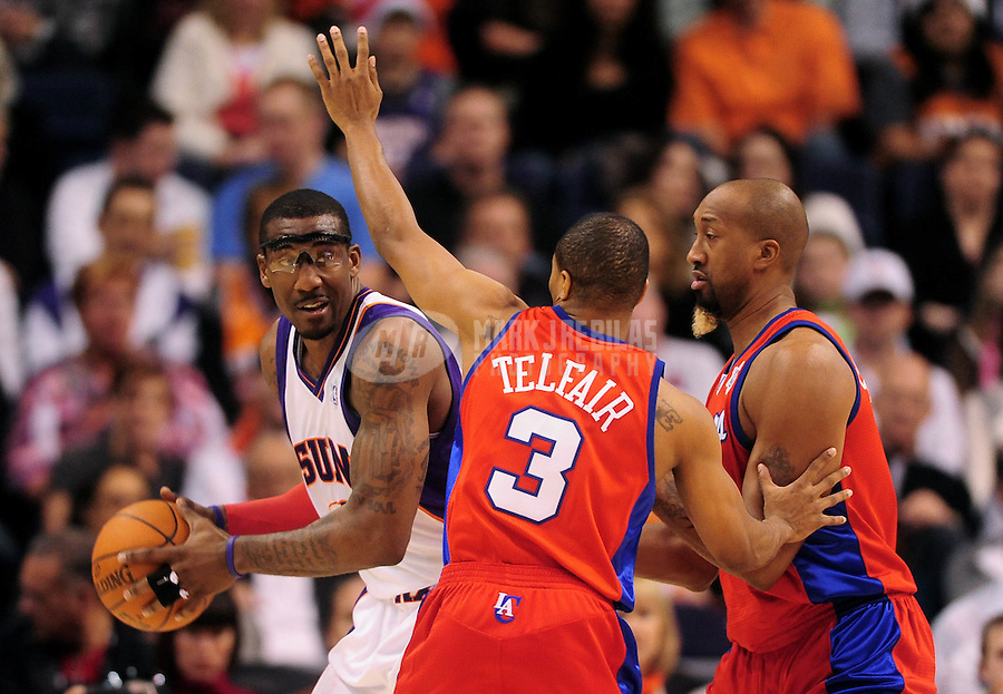 Dec. 25, 2009; Phoenix, AZ, USA; Phoenix Suns forward (1) Amare Stoudemire tries to move the ball as he is defended by Los Angeles Clippers guard (3) Sebastian Telfair and forward Brian Skinner at the US Airways Center. The Suns defeated the Clippers 126-93. Mandatory Credit: Mark J. Rebilas-
