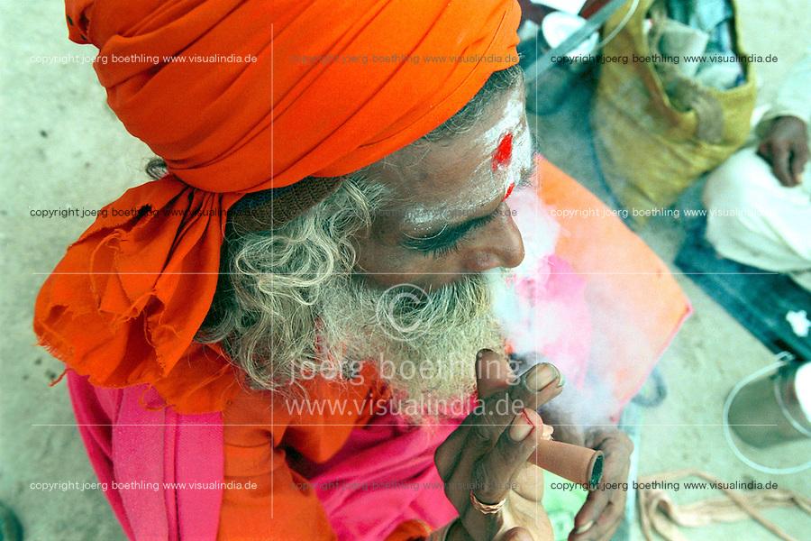 INDIA, Maharashtra, Nasik, Hindu festival Kumbha Mela, holy man Sadhu smoking Ganja, Cannabis / INDIEN, Nasik, Hindu Festival Kumbh Mela, Wandermoenche Sadhus rauchen Marihuana mit Shillum