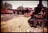 A rusting RGS #461 K-27 at Ridgway yard along with other equipment, cabooses, gons and Goose #5 in the roundhouse.<br /> RGS  Ridgway, CO  ca. 1952