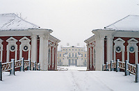 The imposing facade of Rundale Palace is glimpsed through the snow between the red and white painted stucco buildings of the stables