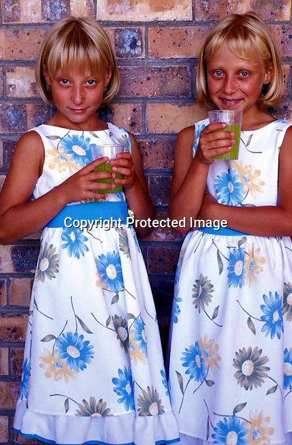 dippchi00294 Children. Identical Afrikaner twin sisters in Orania drinking a cool drink. Dress in the same clothes. .©Per-Anders Pettersson/iAfrika Photos