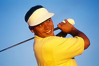 Asian American golfer after driving the ball.